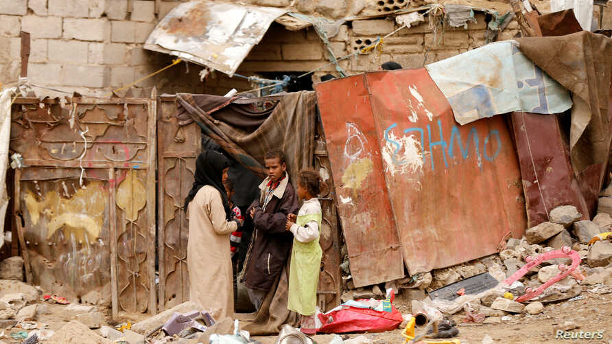 Children displaced from the Red Sea port city of Hodeida stand outside their shelter in Sanaa, Yemen, July 18, 2018.
