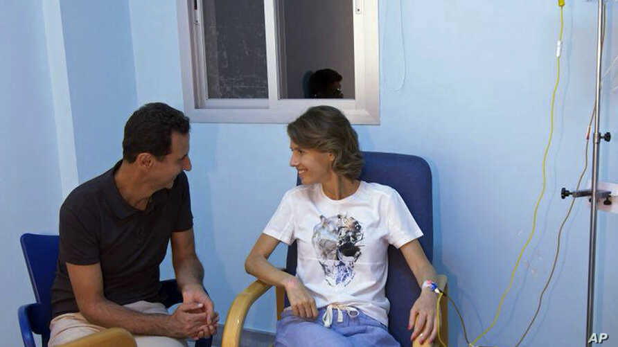This photo posted Aug 8, 2018 on the official Facebook page of the Syrian Presidency, shows  President  Assad sitting next to his wife Asma Assad with an IV in her left arm in what appears to be a hospital room, in Syria.