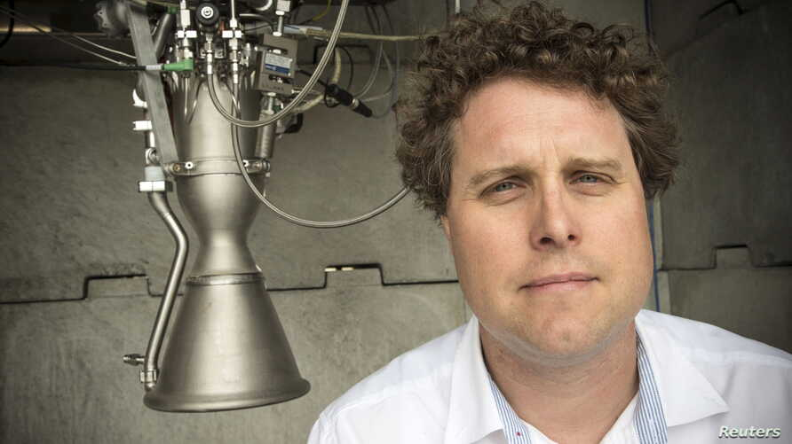 FILE - Rocket Lab CEO Peter Beck poses alongside a Rutherford rocket engine in Auckland, New Zealand, Oct. 20,  2015.