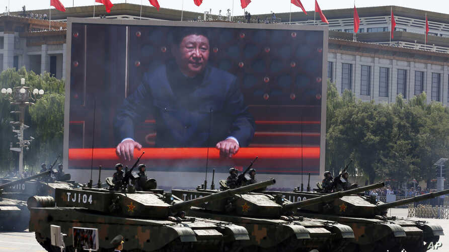 FILE - Chinese President Xi Jinping is displayed on a screen as Type 99A2 Chinese battle tanks take part in a parade commemorating the 70th anniversary of Japan's surrender during World War II, Tiananmen Gate, Beijing, China.