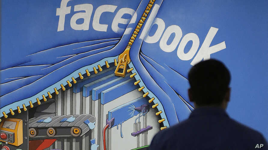 FILE - A Facebook employee walks past a sign at Facebook headquarters in Menlo Park, California, March 15, 2013.