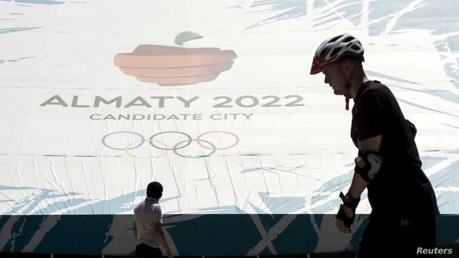 People walk past a banner promoting Almaty candidate city for 2022 Winter Olympic Games at the Medeu skating oval in Almaty, Kazakhstan, July 26, 2015.