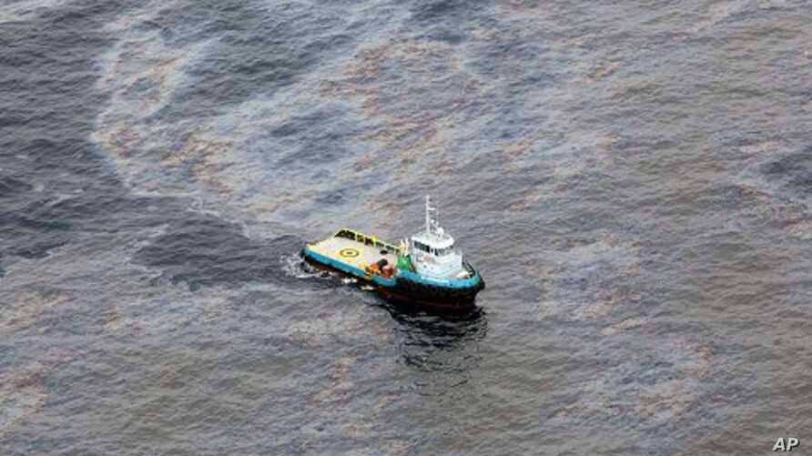This photo taken Nov. 18, 2011 and released by Rio de Janeiro's government, shows an aerial view of a boat crossing an area of an oil spill in an offshore field operated by Chevron at the Bacia de Campos, in Rio de Janeiro state, Brazil.