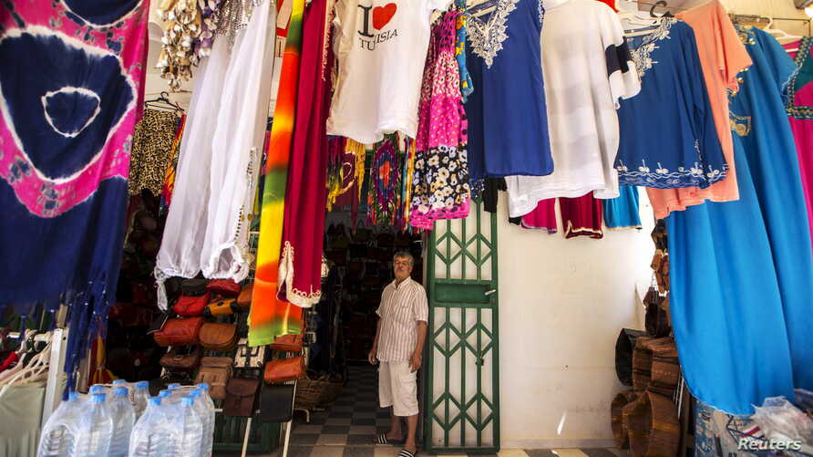 Tunisian shopkeeper Aghmi Bubaker speaks with Reuters journalists at his shop in Sousse, Tunisia, June 30, 2015.