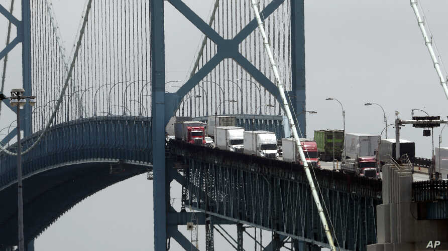 FILE - In this June 12, 2018, photo, trucks cross the Ambassador Bridge from Windsor, Ontario into Detroit. In nearly a quarter-century since NAFTA was approved, a complex chain of automotive parts makers has sprung up on both of the U.S.-Canada bord