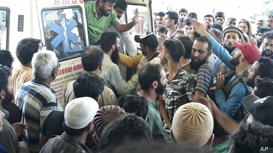 A crowd gathers around an ambulance carrying victims killed in a bus accident near Kishtwar, about 217 kilometers (135 miles) southeast of Srinagar, Indian-controlled portion of Kashmir, Sept. 14, 2018.
