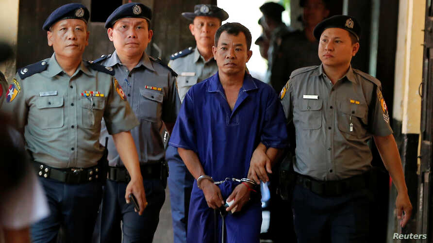 Detained Police Captain Moe Yan Naing is escorted by police after arriving for a court hearing in Yangon, Myanmar, May 9, 2018.