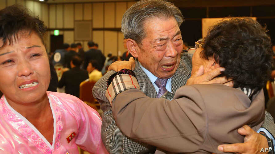 South Korean Min Ho-Sik, center, 84, hugs his North Korean relative Min Eun-Sik, right, 81, during a reunion meeting of family members separated after the Korean War at the Mount Kumgang resort on the North's southeastern coast, Oct. 20, 2015.