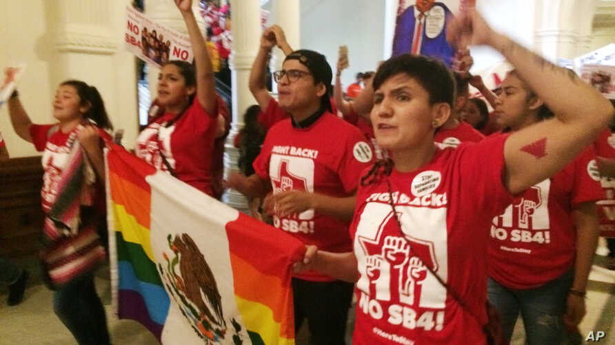 Demonstrators march in the Texas Capitol, May 29, 2017, protesting the state's newly passed anti-sanctuary cities bill, in Austin, Texas.