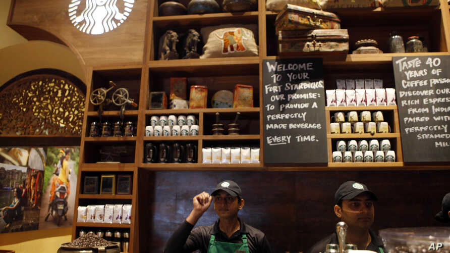 Indian employees of the newly inaugurated first India outlet of Starbucks work at a counter in Mumbai, India, October 19, 2012.