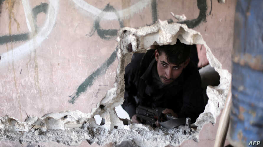 A Syrian rebel fighter from the Failaq al-Rahman brigade mans a position on the frontline against regime forces in the town of Arbin in the eastern Ghouta region on the outskirts of the capital Damascus, Feb. 26, 2016.