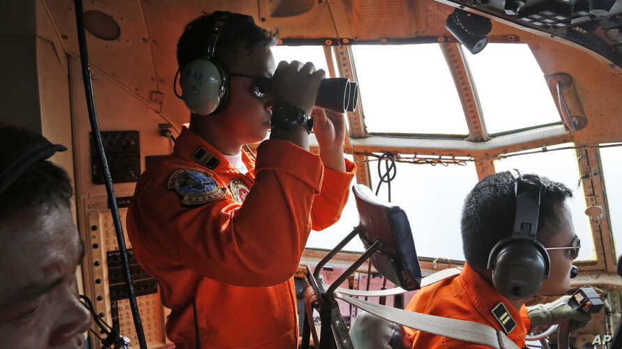 A crew of an Indonesian Air Force C-130 airplane of the 31st Air Squadron uses a binocular to scan the horizon during a search operation for the missing AirAsia flight 8501 jetliner over the waters of Karimata Strait in Indonesia, Monday, Dec. 29, 20...