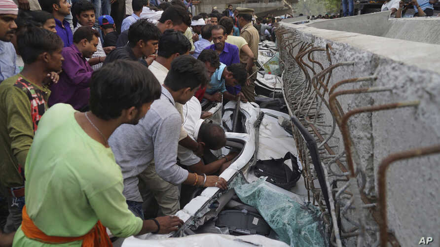 People look for survivors inside vehicles crushed when a section of an under construction overpass collapsed in Varanasi, India, May 15, 2018.