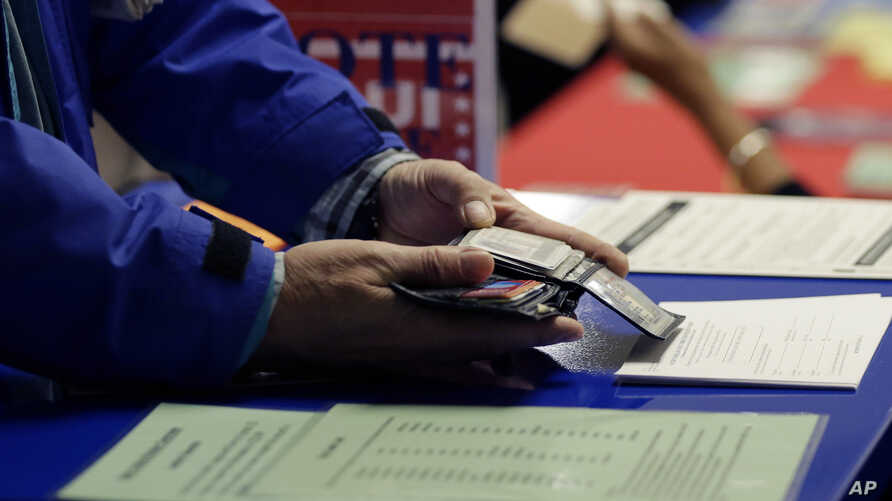 FILE -  a voter shows his photo identification to an election official at an early voting polling site, in Austin, Texas.