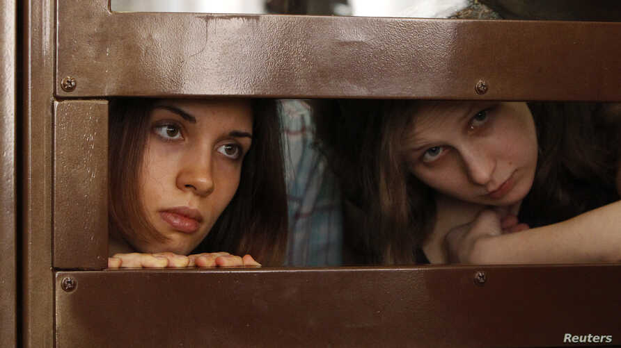 """Nadezhda Tolokonnikova (L) and Maria Alyokhina, members of female punk band """"Pussy Riot"""", look out from the defendent's cell in a courtroom in Moscow July 30, 2012."""
