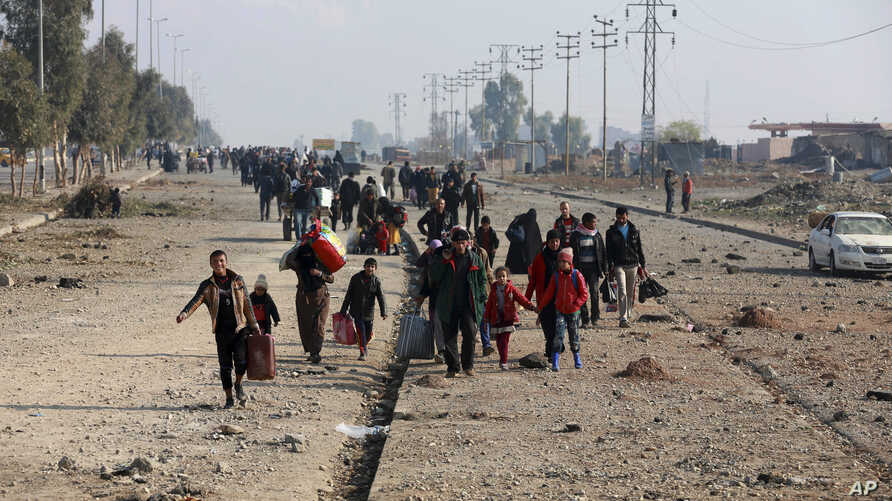 Displaced Iraqis, who fled fighting between Iraqi security forces and Islamic State militants, return to their homes in neighborhoods retaken by Iraqi government forces in the eastern side of Mosul, Iraq, Wednesday, Jan. 4, 2017.