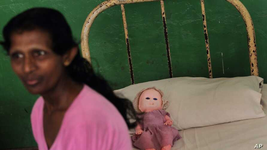 Resident of Half Way Home, a government-run home for the mentally ill located inside a mental health hospital premise, sits on her bed in Mulleriyawa, on the outskirts of Colombo, Sri Lanka, April 2, 2013.