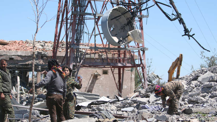 Fighters from the Kurdish People's Protection Units (YPG) inspect the damage at their headquarters after it was hit by Turkish airstrikes in Mount Karachok near Malikiya, Syria, April 25, 2017.