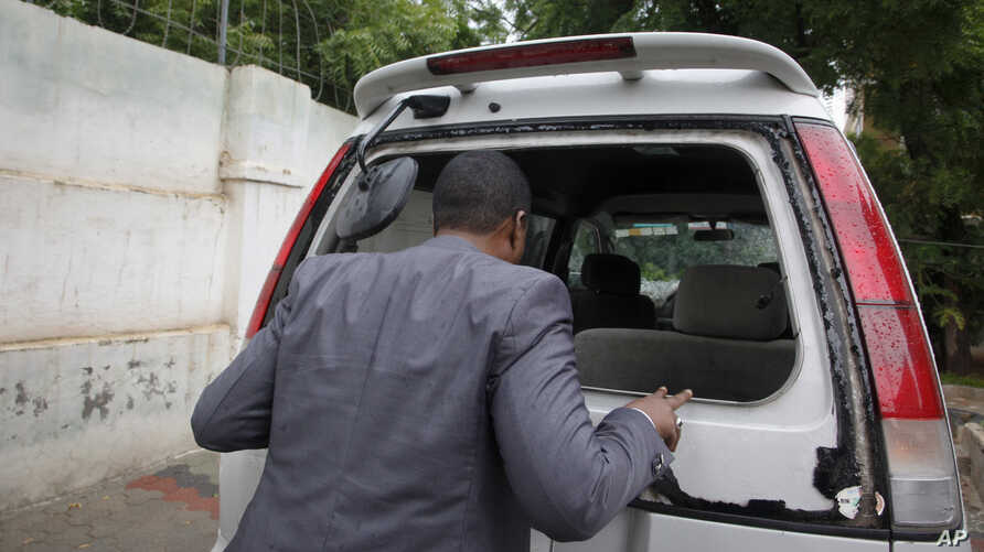 Abdiqadir Dulyar, director for the Somali television station Horn Cable, looks at the smashed window of a car that was carrying journalists working for his station in Mogadishu, May 3, 2016. Unidentified gunmen opened fire on the car last week but no...
