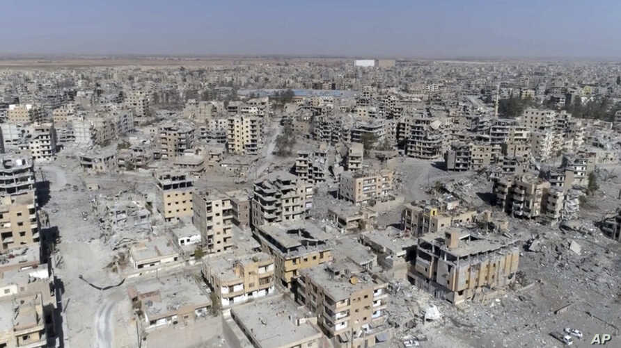 This Oct. 19, 2017, frame grab made from drone video shows damaged buildings in Raqqa, Syria.
