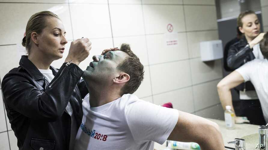 Yulia, wife of Russian opposition leader Alexei Navalny treats him after unknown attackers doused him with green antiseptic outside a conference venue in Moscow, Russia, April 27, 2017.