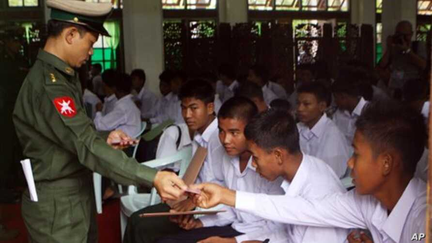 A Burma soldier (L) gives the national identity card to child soldiers who were recruited into the army before reaching the age of 18, during a ceremony where they were handed over to their parents and guardians in Rangoon, September 3, 2012.