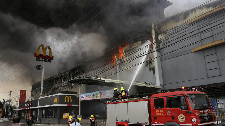 Firemen battle a fire that rages at a shopping mall, Dec. 23, 2017, in Davao city, southern Philippines.