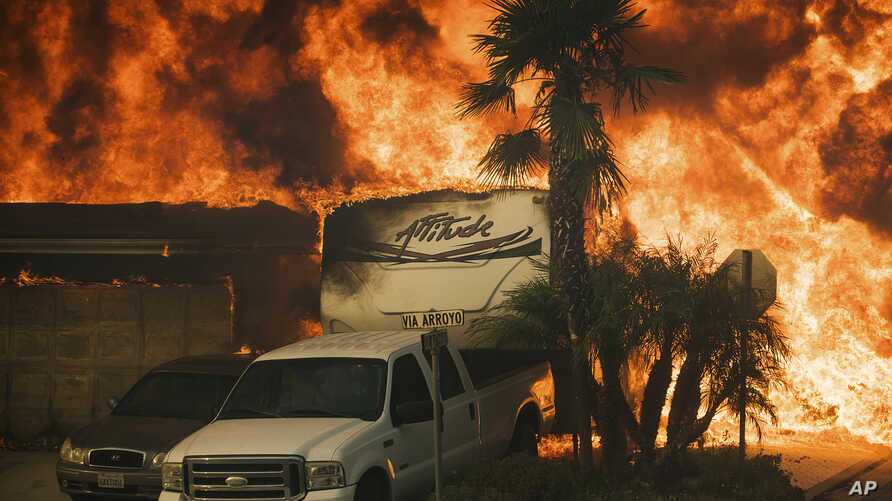 Flames consume a home on Via Arroyo as a wildfire rages in Ventura, Calif., on Tuesday, Dec. 5, 2017.