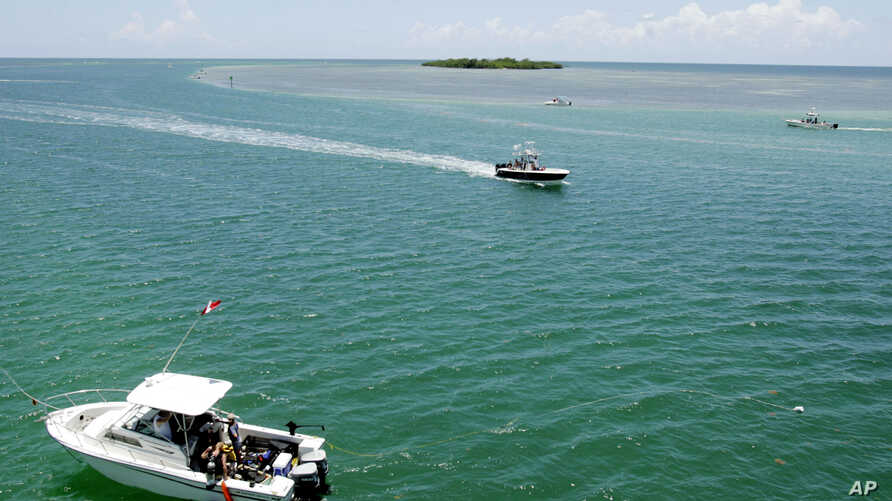 FILE - Boats hoisting red-and-white dive flags dot the waters off the Florida coast, July 26, 2006.