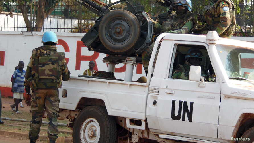 U.N. peacekeepers take a break as they patrol along a street during the presidential election in Bangui, the capital of Central African Republic, Dec. 30, 2015.