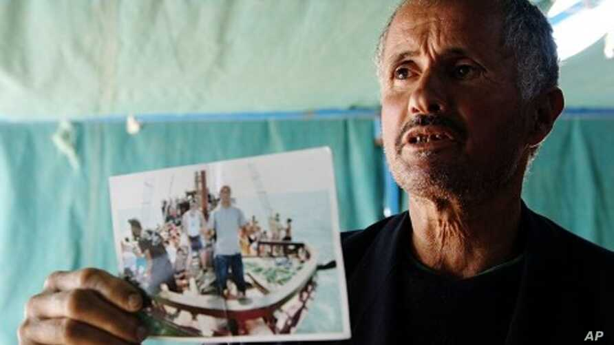 Tunisian man shows a photograph of his relative, who died while trying to reach Italy illegally, at coastal town Zarzis in southeastern Tunisia, February 18, 2011