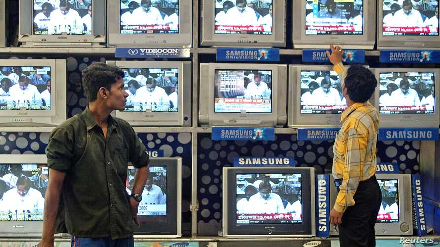 Indian salesman tunes televisions at an electronics shop as government official on screen pledges to boost spending for rural infrastructure, 2006 (file photo).