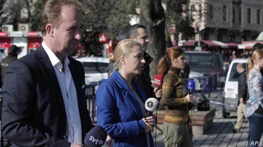 Members of the media report at the area of an explosion in the historic Sultanahmet district of Istanbul, Tuesday, Jan. 12, 2016.