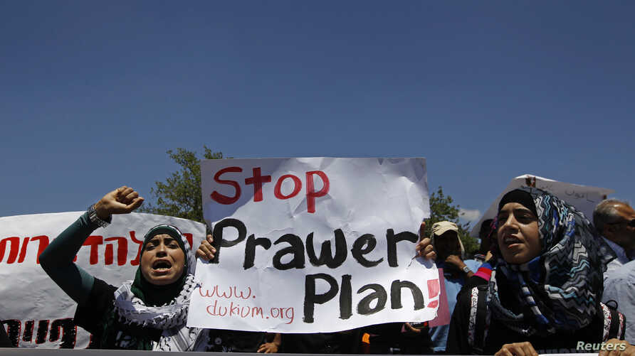Bedouins hold signs as they take part in a protest against a plan to formally recognise Bedouin communities in the Negev desert, outside the Knesset, the Israeli parliament, in Jerusalem May 27, 2013.