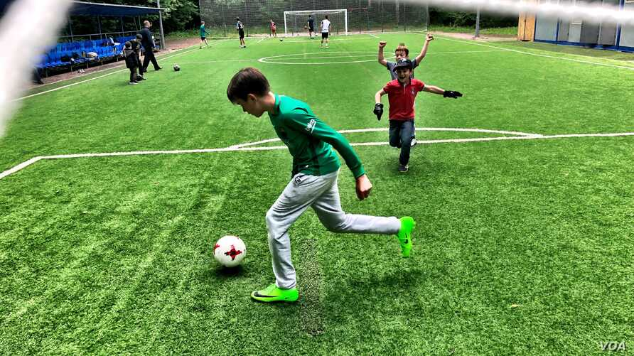 Kids play a pickup game of football in a central Moscow park. Russia hosts World Cup 2018 amid concerns its team may fair poorly. (C.Maynes for VOA)