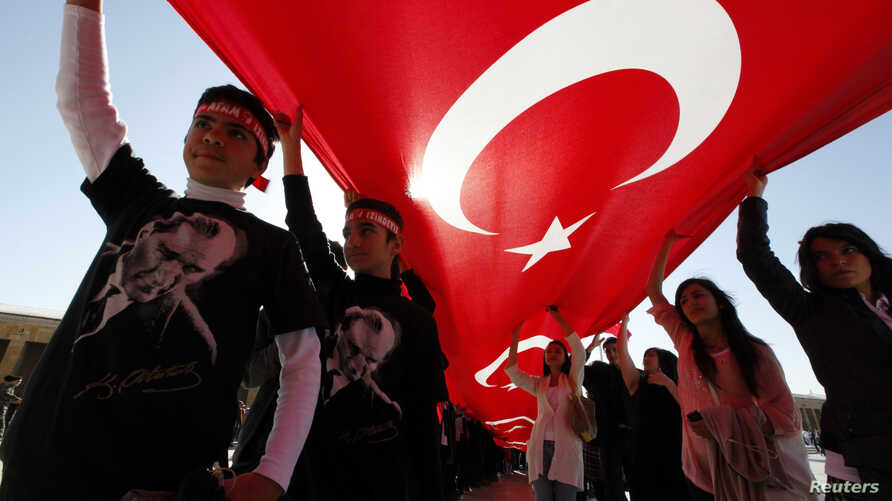 Youth are seen in Ankara holding Turkey's national flag and wearing T-shirts adorned with the image of Mustafa Kemal Ataturk, secular Turkey's founder (file photo).