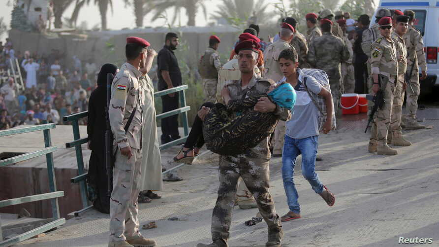 An Iraqi soldier carries a girl displaced by fighting in Ramadi across a bridge at the outskirts of Baghdad, May 19, 2015.