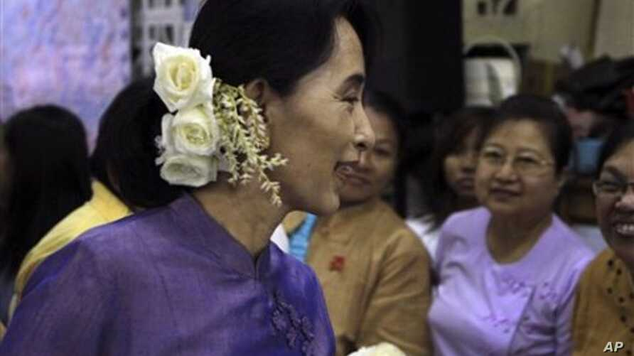 Burma democracy icon Aung San Suu Kyi talks to supporters before celebrations for the 96th birthday anniversary of her late father, General Aung San, and Myanmar Children Day at her National League for Democracy party's headquarters, in Rangoon, Febr
