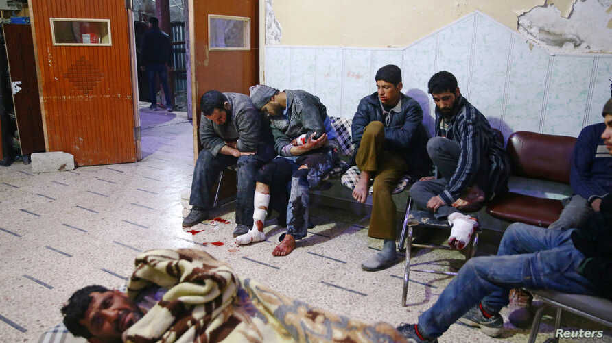 People sit a medical point in the besieged town of Douma, Eastern Ghouta, Damascus, Syria, Feb. 20, 2018.