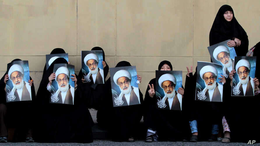 FILE- Anti-government protesters hold posters of top Shiite cleric Sheik Isa Qassim to show their support for him, in Karrana, Bahrain, just outside the capital of Manama, May 17, 2013.
