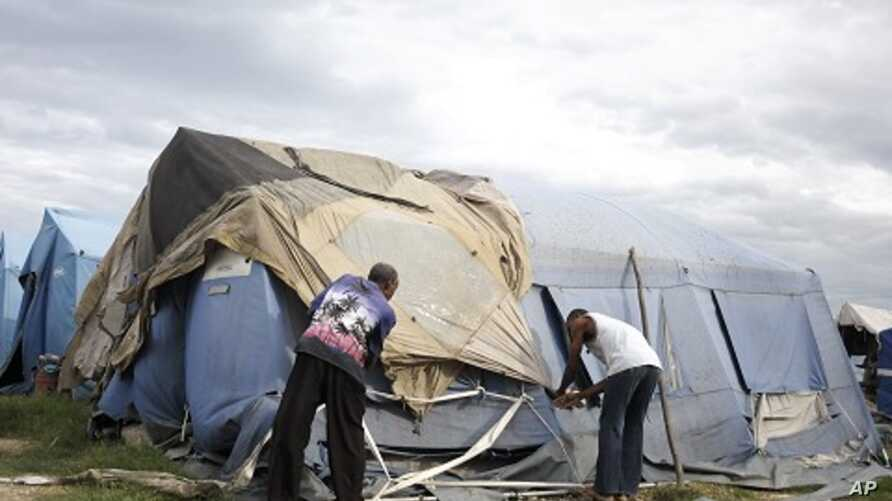 Men try to tie down their tent, which serves as their home, with scraps of material in the slum area of Cite Soleil August 4, 2011.