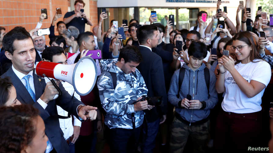 Venezuelan opposition leader Juan Guaido, whom some nations have recognized as the country's rightful interim ruler, talks as he arrives to attend a meeting with students in Caracas, Venezuela, Feb. 11, 2019.