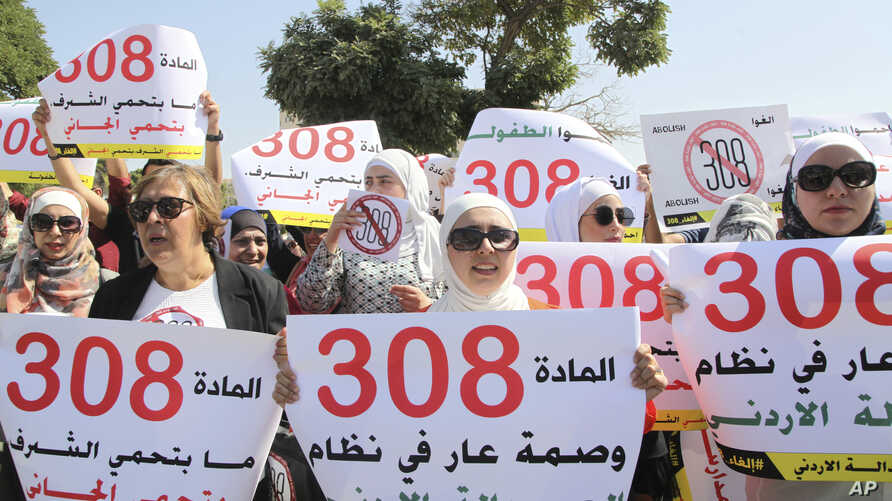 Women activists protest in front Jordan's parliament in Amman on August 1, 2017 with banners calling on legislators to repeal a provision that allows a rapist to escape punishment if he marries his victim.