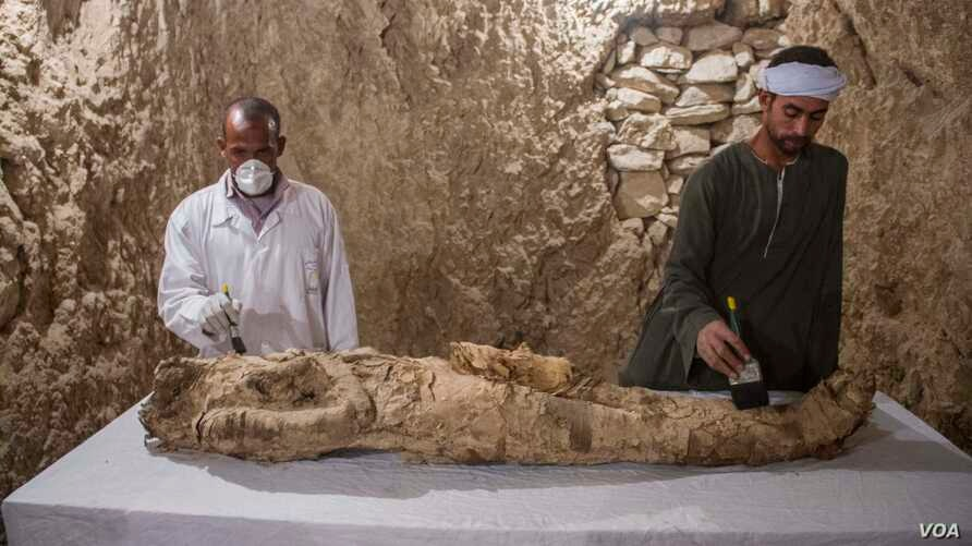 Egyptian excavation workers restore a mummy in a newly discovered tomb, known as Kampp 150, in the Draa Abul Naga necropolis on Luxor's West Bank, Egypt, Dec. 9, 2017.(H. Elrasam/VOA)