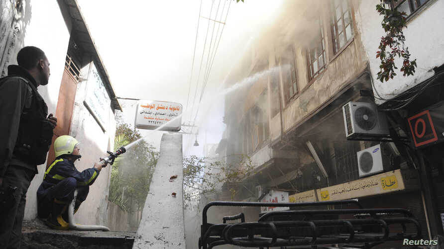 Firefighters try to extinguish a fire after a mortar bomb landed in Damascus, in this handout photograph distributed by Syria's national news agency SANA, Oct. 15, 2013.