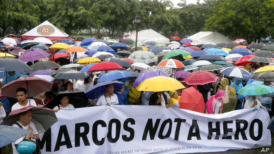 Protesters display a banner as they gather for a rally at Rizal Park in Manila to oppose the burial of the late Philippine dictator Ferdinand Marcos at the Heroes' Cemetery, Aug. 14, 2016.
