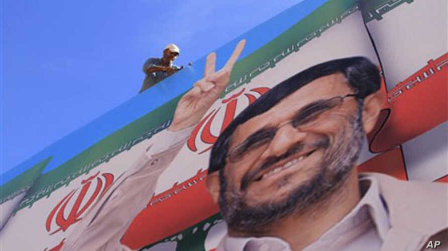 A worker fixes a huge poster of Iranian President Mahmoud Ahmadinejad during preparations for his visit to the southern village of Bint Jbeil, Lebanon, 12 Oct 2010