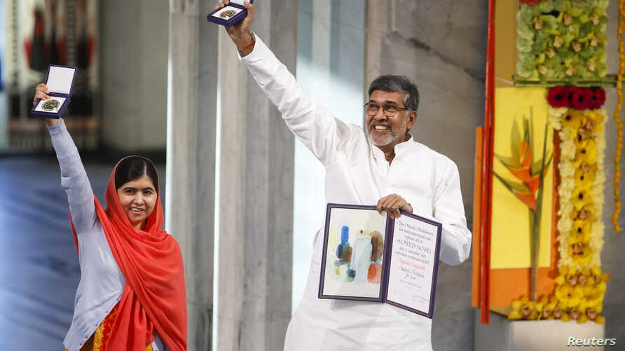 Nobel Peace Prize laureates Malala Yousafzai and Kailash Satyarthi pose with their medals during the Nobel Peace Prize awards ceremony at the City Hall in Oslo, Dec. 10, 2014.