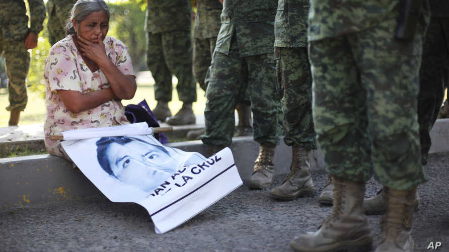 FILE - The mother of missing college student Adan Abarajan de la Cruz sits at the foot of soldiers outside a military base during a protest by the families of 43 missing students over the army's alleged responsibility or lack of response to the stude