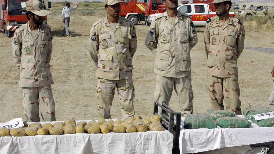 FILE - Iranian police officers stand behind narcotics that were seized at the Milak border in southeastern Iran, Oct. 10, 2012.